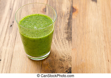 green smoothie in glass on brown wooden background