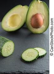 Green smoothie ingredients - avocado, cucumber on a dark background