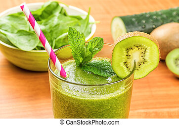 Green smoothie with a drinking straw and fresh ingredients