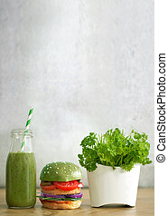 Green smoothie with burger and salad