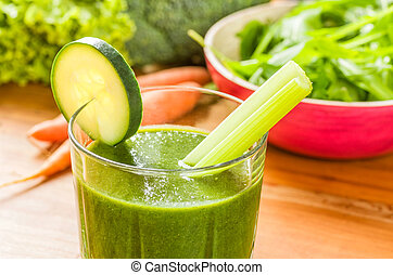 Green smoothie with fresh vegetables on a wooden background