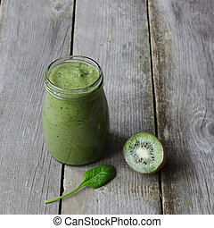 Green smoothie with kiwi and leaf of spinach on wooden background