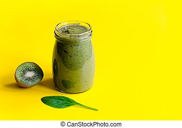 Green smoothie with kiwi and leaf of spinach on yellow background