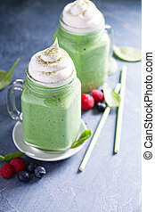 Green smoothie with whipped topping in mason jars