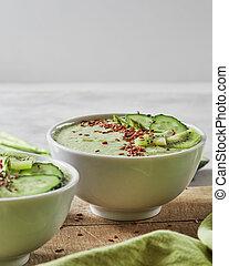 Green smoothies with a cucumber, kiwi and flax seeds in a plate on an old wooden board. Vegetarian food