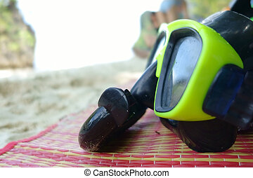 Green Snorkel and Diving mask on Mat at the sea.