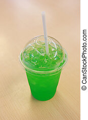 Green soda in the glass.