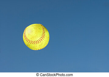 Green softball - A practice softball flys through the air...