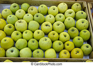 Green sour apples in the wooden tray