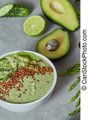 green spinach smoothy bowl topped with cucumber, avocado and flax seeds on stone background