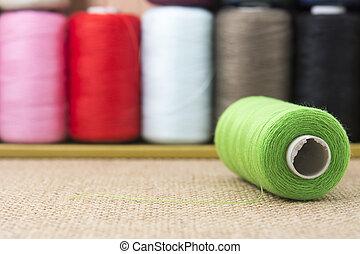 Green spools of thread on sackcloth