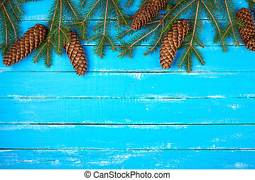 green spruce branches with brown cones on a blue wooden background from boards