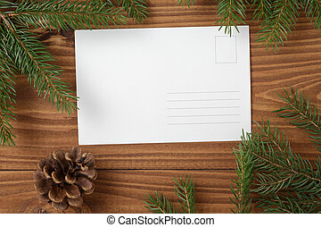 green spruce twig on wooden plank witc greeting card