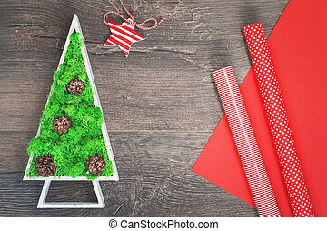 Green stabilized Christmas tree and red gift wrapping paper