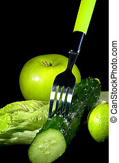group of green vegetables and fruits with fork over black background