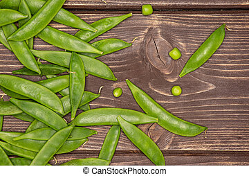 Green sugar snap pea on brown wood - Lot of whole fresh ...