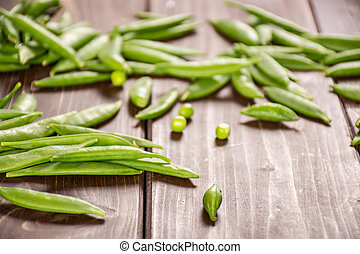 Green sugar snap pea on brown wood - Lot of whole young ...