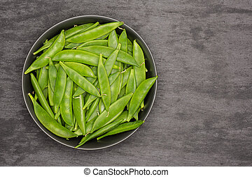 Green sugar snap pea on grey stone - Lot of whole green ...