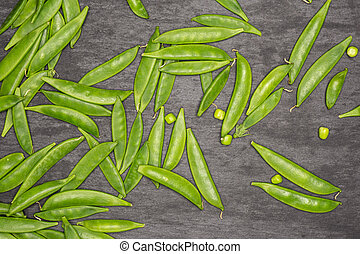 Green sugar snap pea on grey stone - Lot of whole young ...