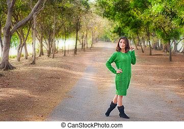 Green suit Asian woman in garden