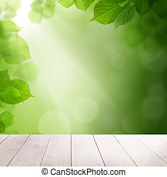 Green summer leaves and abstract bokeh light with white wooden board background