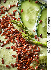 Green superfood smoothies with flax seeds and cucumber macro photo
