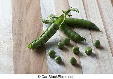 Green sweet peas in a pile on brown wood surface