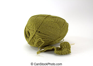 Green tangle of natural wool for needlework with a crochet hook on a white background