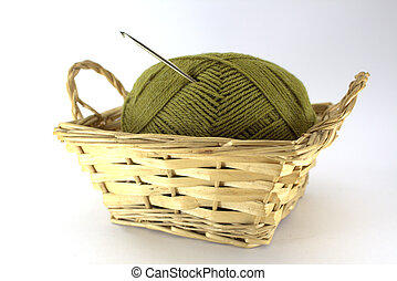 Green tangle of natural wool for needlework with a crocheted crochet stuck in it in a wicker basket