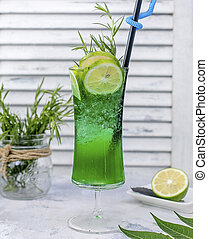 Green tarragon drink with lime slices, tarragon in standing glass