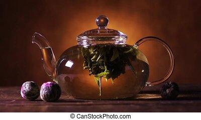 Green tea flower bud blooming in glass teapot - Green...
