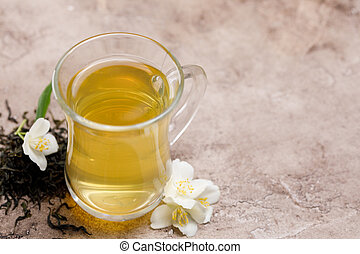 Green tea in a glass cup and fresh jasmine flowers nearby.
