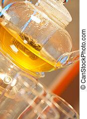 Green tea in a glass teapot