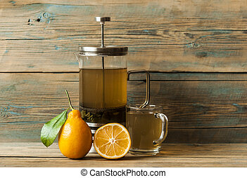 Green tea in a glass with yellow lemon