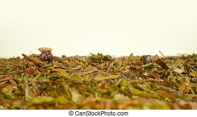 Green tea leaves scattered on the table with white background