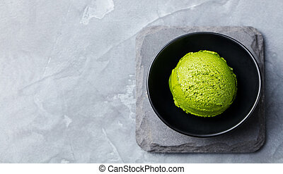 Green tea matcha ice cream scoop in black bowl on a grey stone background. Copy space. Top view.
