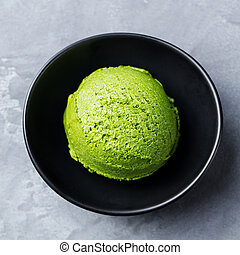 Green tea matcha ice cream scoop in black bowl on a grey stone background. Top view. Close up.