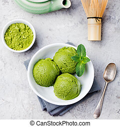 Green tea matcha ice cream scoop in white bowl. Grey stone background. Top view.