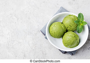 Green tea matcha ice cream scoop in white bowl on a grey stone background. Copy space Top view