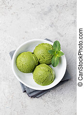 Green tea matcha ice cream scoop in white bowl on a grey stone background Copy space Top view.