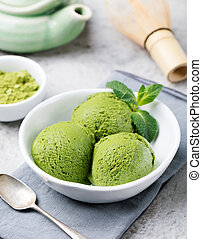 Green tea matcha ice cream scoop in white bowl on a grey stone background