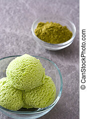 Green tea matcha ice cream scoops in crystal bowl on gray stone background