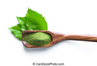 green tea powder in spoon on white background