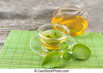 green  tea with mint  on cup of tea and pot