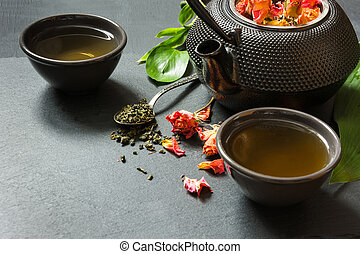 Green tea with rose flower on black slate dish. Close up with copy space.