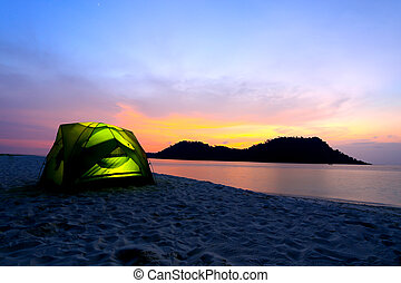 green tent on beach in sunset