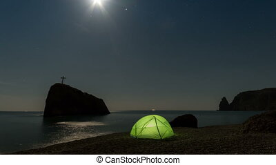 Green tent on the beach at night under the starry sky. Timelapse