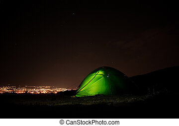 Green tent standing in the night with the light inside