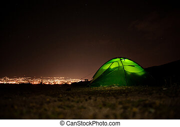 Green tent standing on the hill in the night