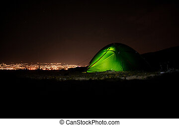 Green tent standing on the hill in the night with the light inside